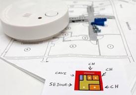 photo : détecteur de fumée à plat sur un plan de masse d'appartement, avec indications de placement